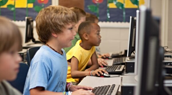 Young children working on computers at school