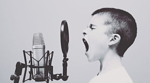 Black-and-white photo of boy screaming into microphone