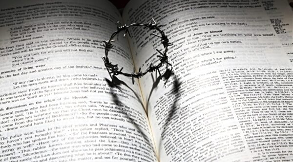 Barbed ring casting heart shadow on Bible