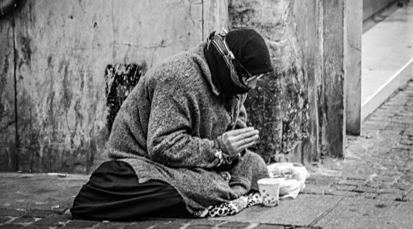 Homeless person sitting on sidewalk and begging