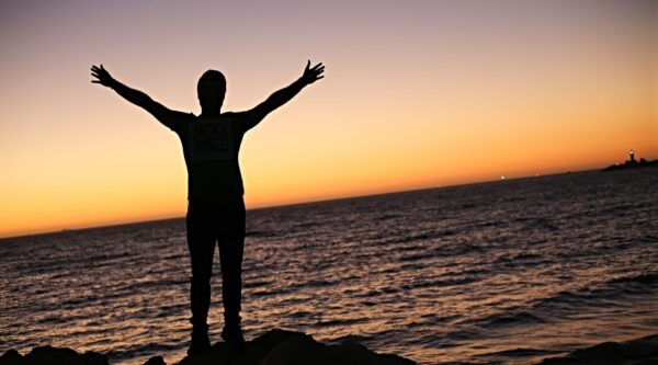 Silhouette of man with arm raised at shoreline