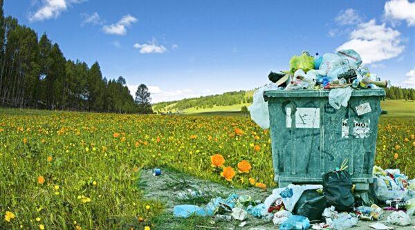Overflowing trash dumpster in field