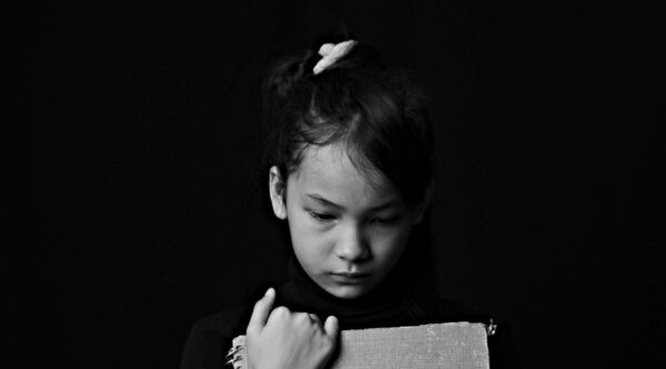 Black-and-white photo of sad girl clutching book