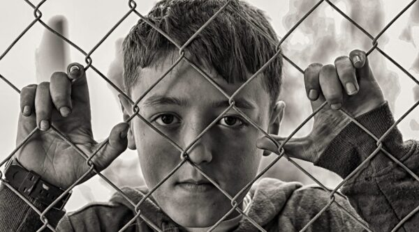 Young boy holding hands and looking through chain-link fence