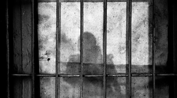 Prison bars with person's shadow on wall