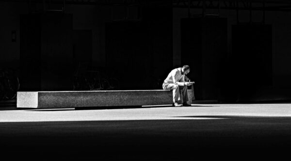 Man sitting on bench alone surrounded by darkness