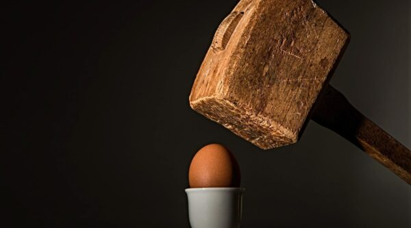 Mallet about to crush egg in serving cup