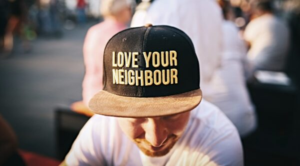"Man wearing with cap with words ""Love Your Neighbour"""