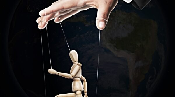 Wooden puppet manipulated by string from hand above