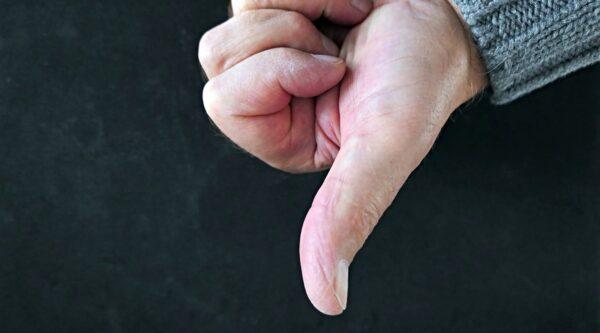 Hand making thumbs-down gesture