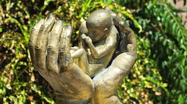 Sculpture of baby between a pair of hands