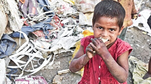 Young impoverished boy eating food