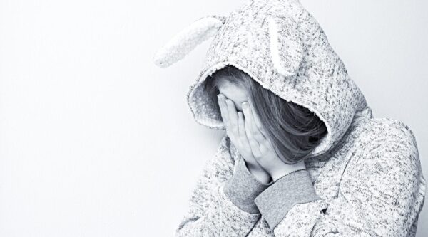 Girl wearing jacket with hands covering face