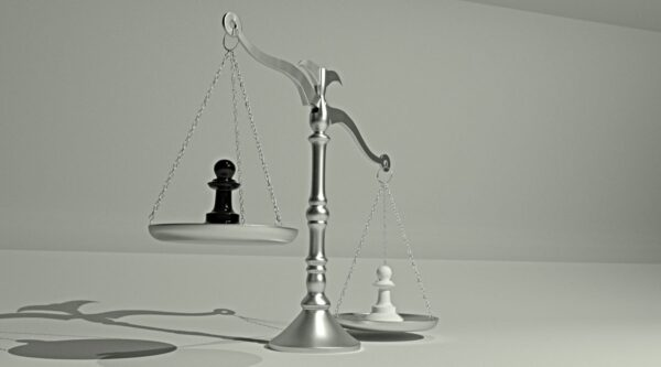 Scales with white pawn outweighing black pawn