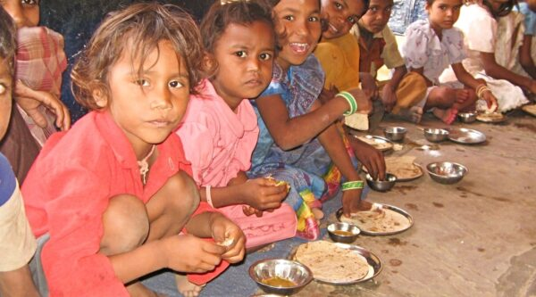 Children squatting in front of plates of food