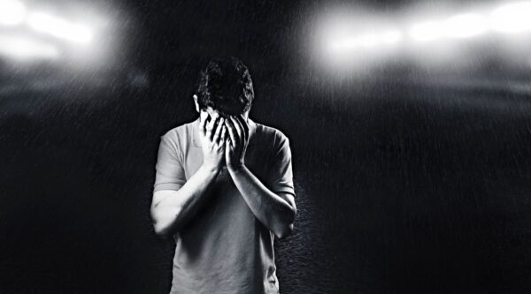 Depressed man with face in hands
