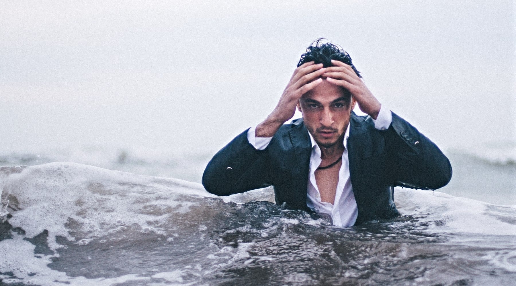 Stressed man standing in ocean