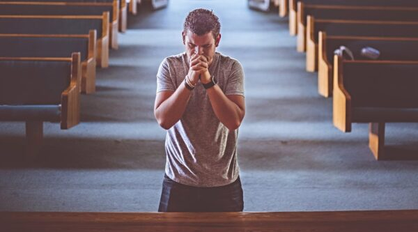 Man on his knees praying at front of sanctuary