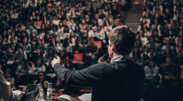Man speaking to crowd in auditorium
