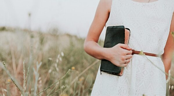 Woman holding Bible in field