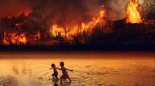 Two children running in river with forest fire in background