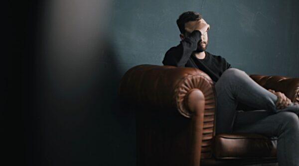 Depressed man sitting alone on sofa