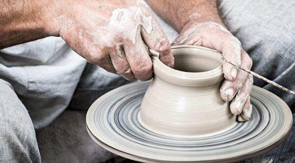 Potter's hands molding clay vessel