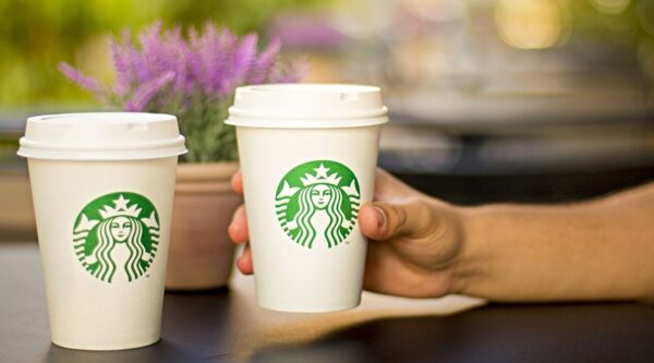 Hand holding one of two Starbucks cups