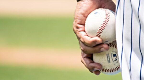 Uniformed pitcher holding two baseballs