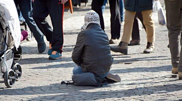 Beggar sitting on walkway as people pass by