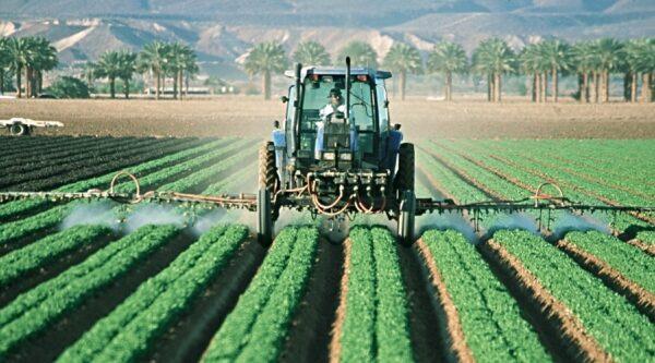 Farmer operating tractor in field