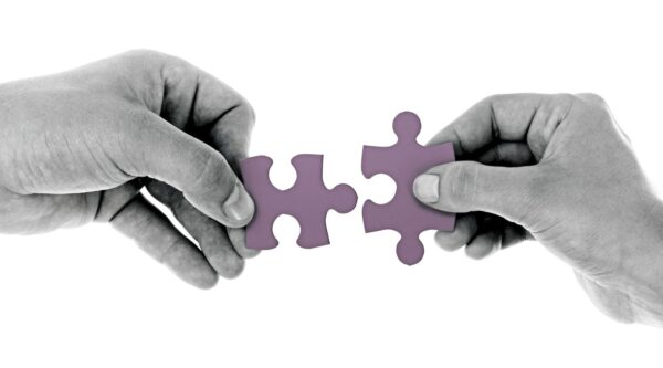 Two hands each holding an interlocking jigsaw puzzle piece