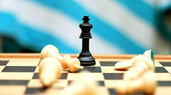 King on chessboard with opposing pieces toppled around it