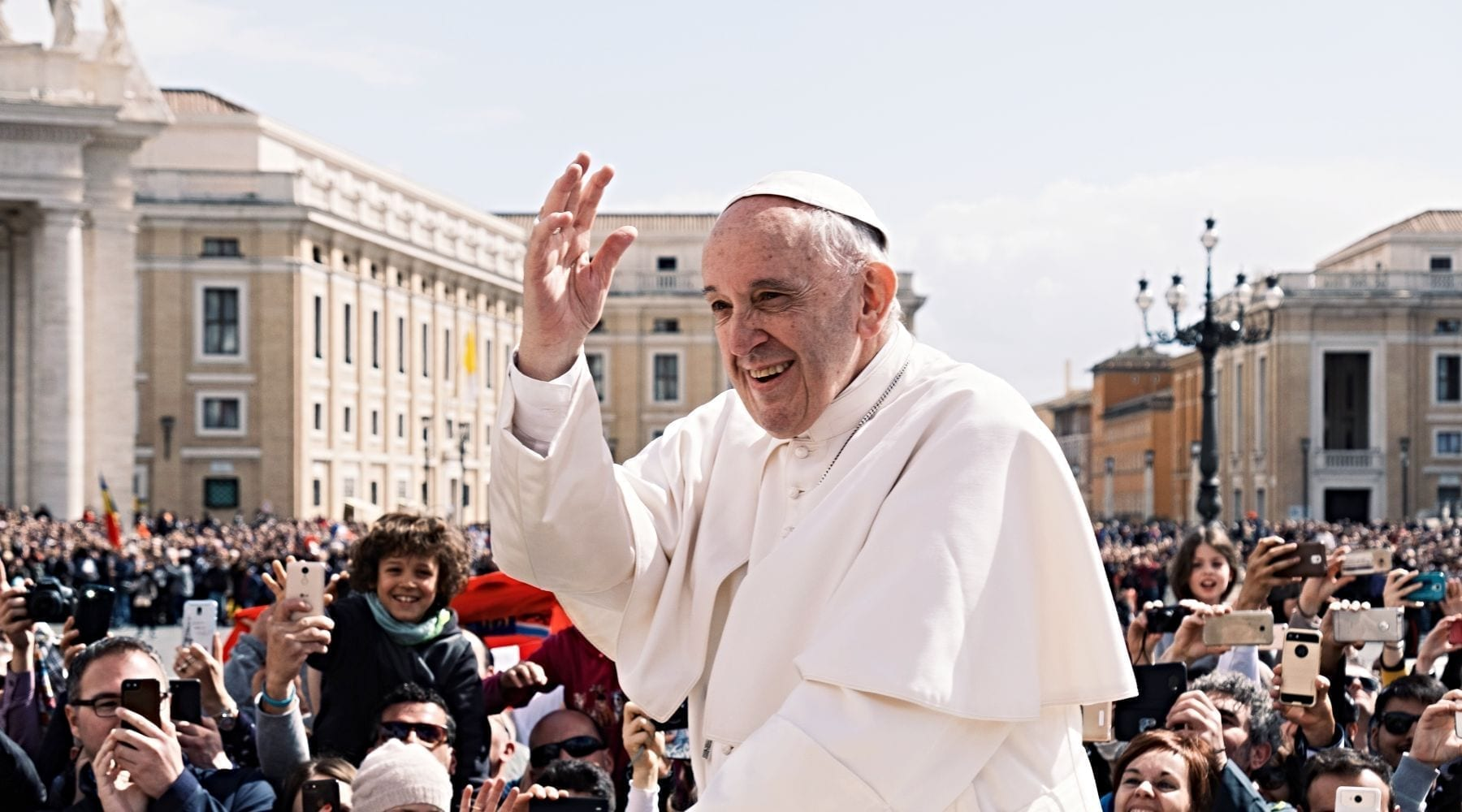 Pope Francis waving in crowd outside