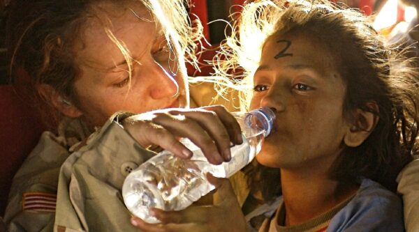 Woman providing drink of bottled water to girl
