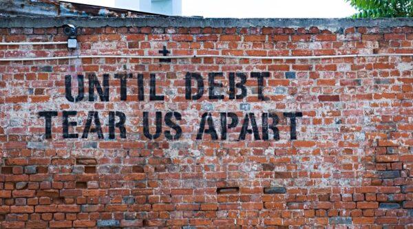 Graffiti about debt written on brick wall