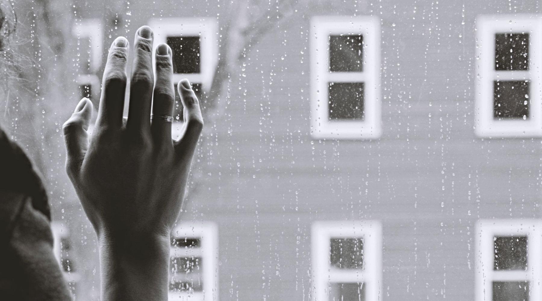 Hand on window splattered with raindrops