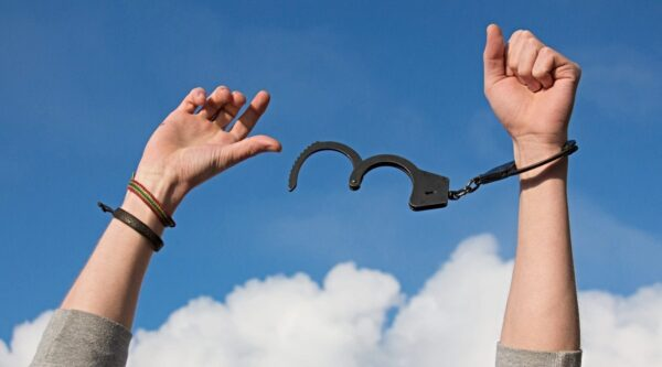 Two arms lifted skyward breaking free of handcuffs