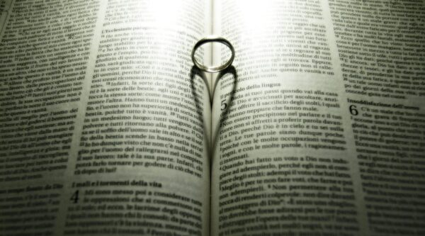 Ring casting heart shadow on pages of Bible