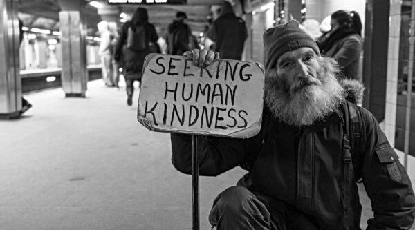 Seated beggar holding sign seeking kindness