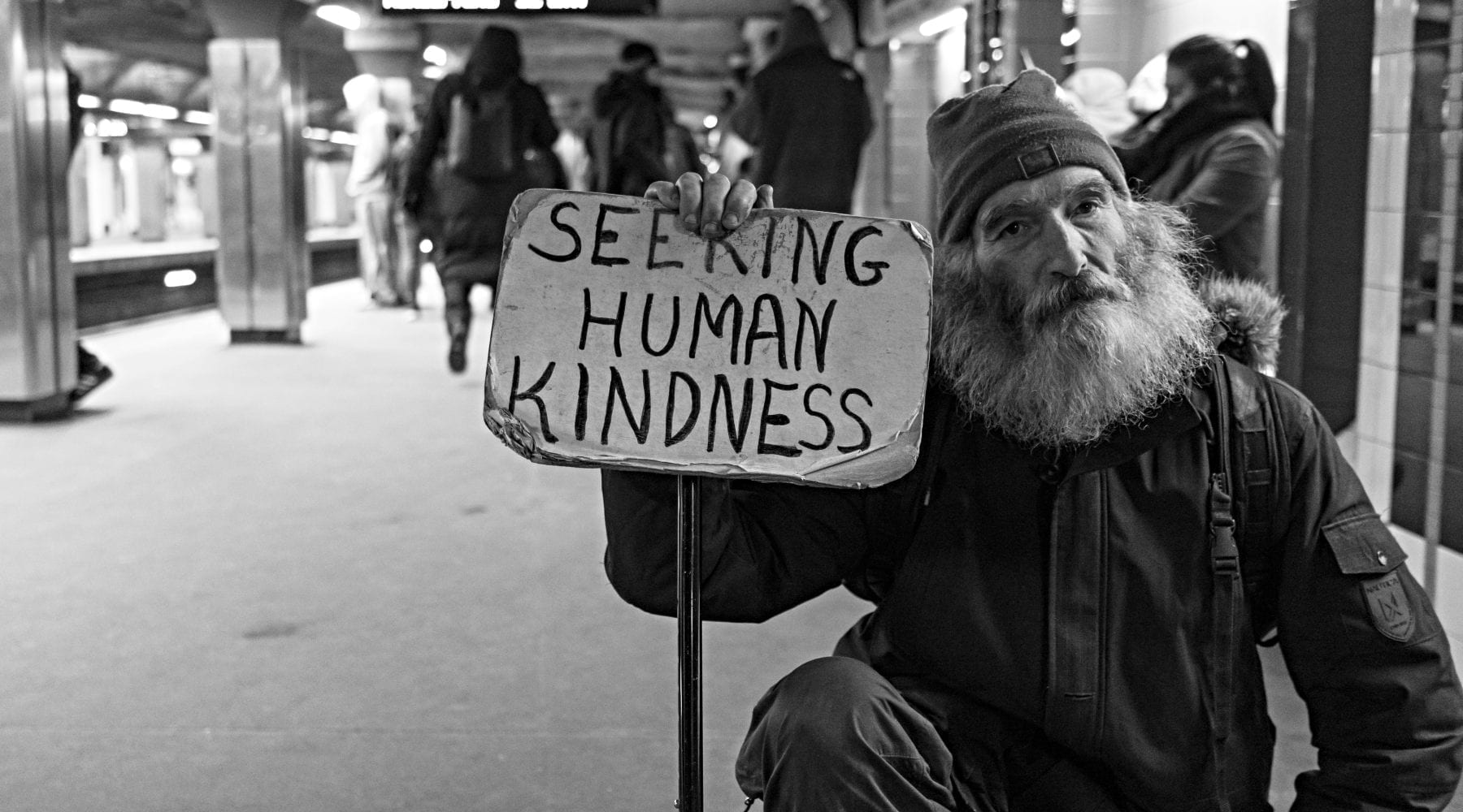 Seated beggar holding sign seeking kindness