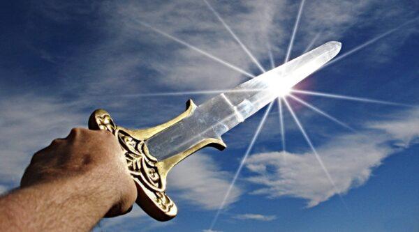 Hand holding sword toward the sky