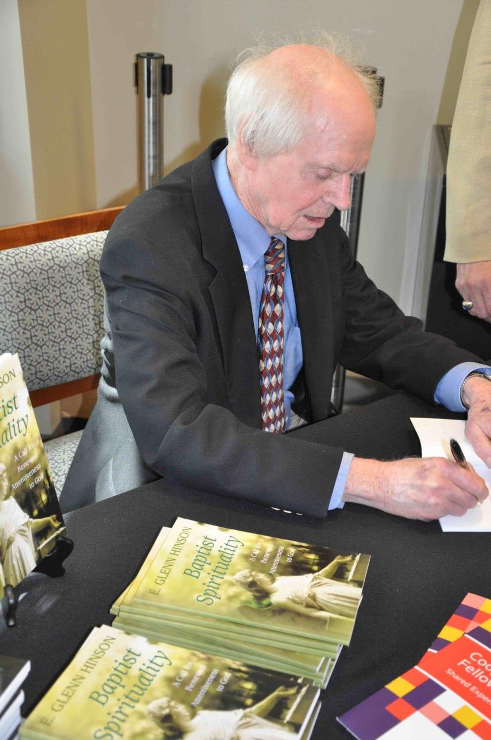 Nurturing Faith author Glenn Hinson signs books.