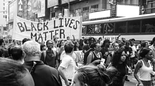 Protesters march on street with Black Lives Matter banner