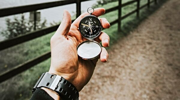 Hand holding compass outdoors and pointing north