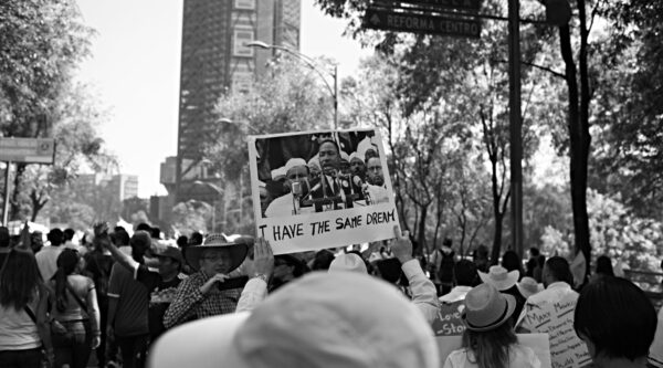 Person holding 'I have the same dream' sign in crowd