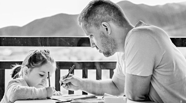 Father and daughter drawing at table