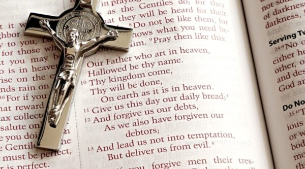 Bible open to Lord's Prayer with crucifix on page