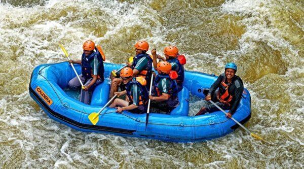 Folks in blue raft navigating rapids in river