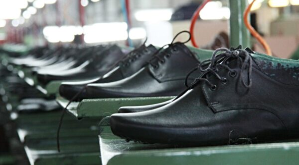 Black dress shoes in line at factory